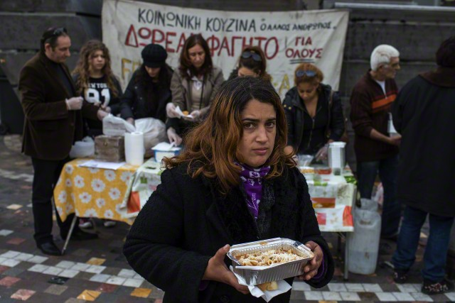 20 Jan 2015, Athens, Attica, Greece --- A woman receives a portion of food at a soup kitchen, organized during the years of the Greek economic crisis by